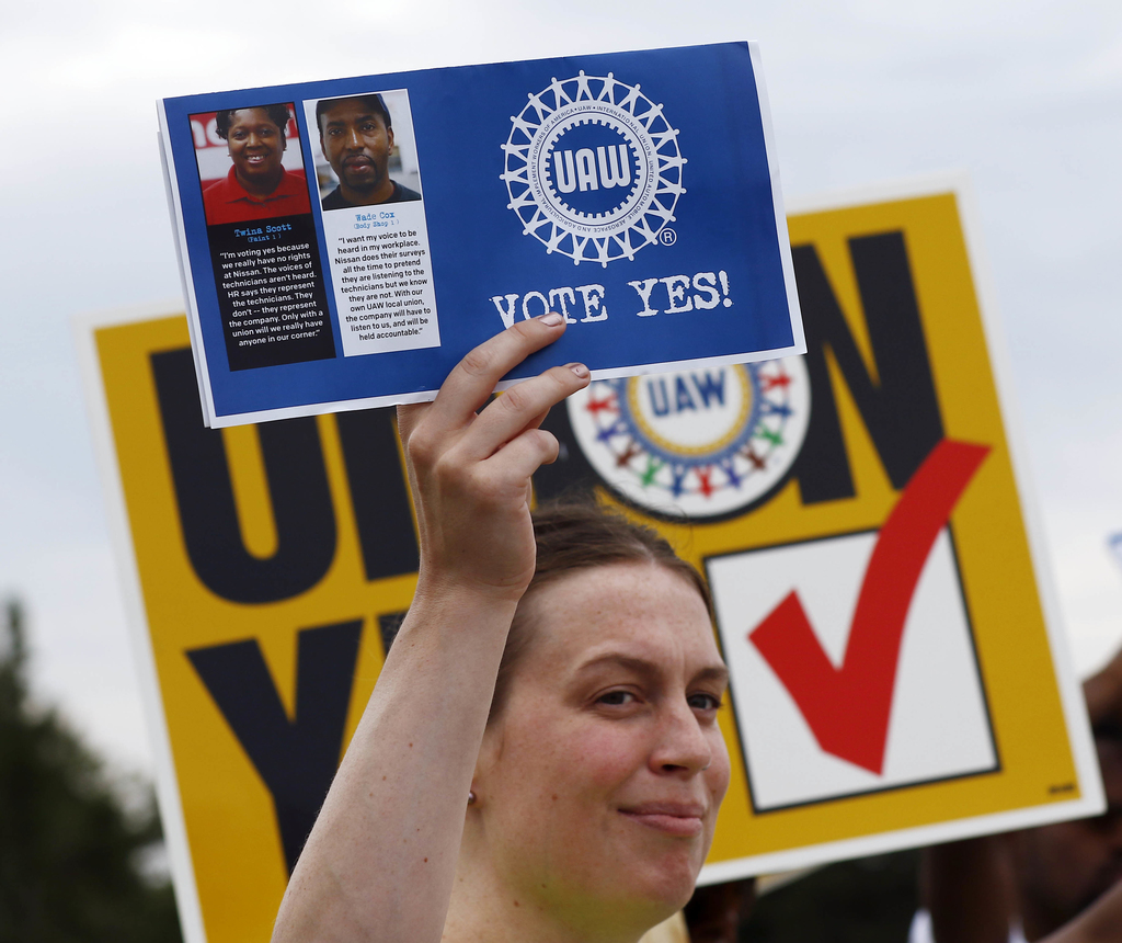 In this Tuesday, Aug. 1, 2017, photo, a UAW member holds up a flyer to be given to Nissan workers as they leave the Nissan vehicle assembly plant in C...