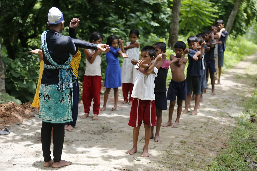 In this July 14, 2017 photo, Bangladeshi children attend a warm up session before a swimming practice in the Shishu Polli Plus area in Sreepur village...