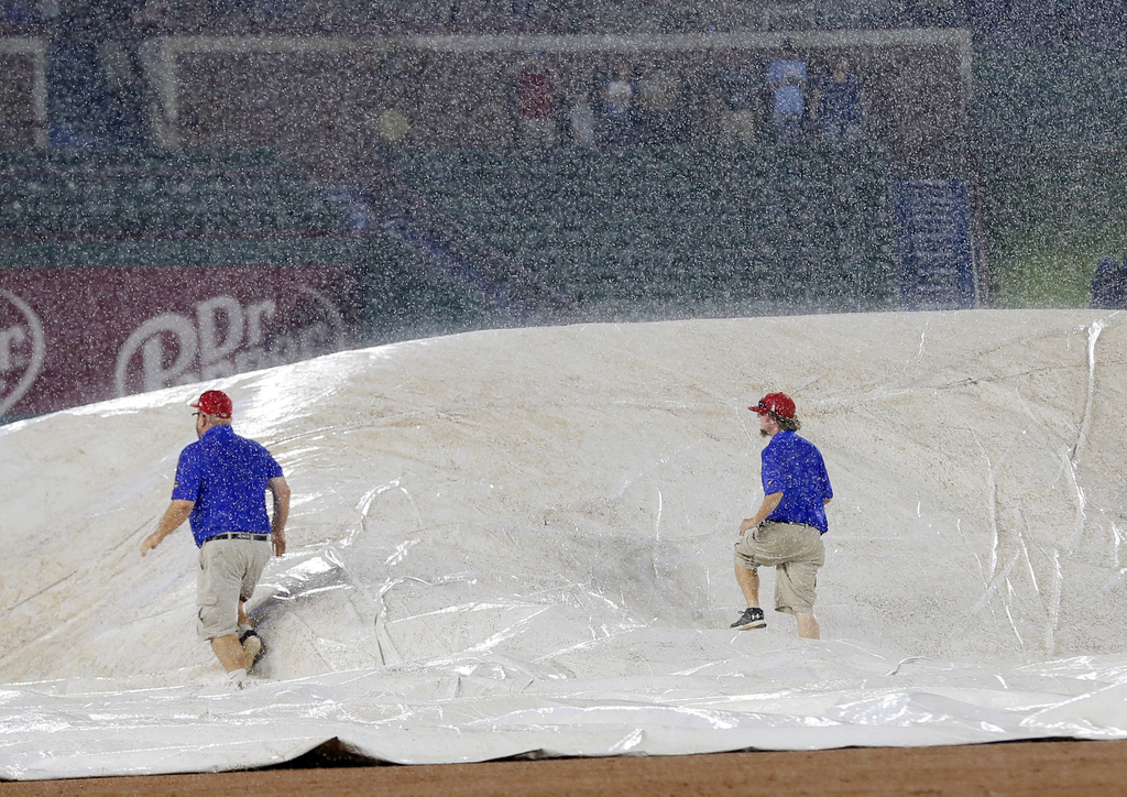 Grounds crew personnel walk over the field tarp trying to remove the air caught beneath as they place it over the field during a heavy rain in the six...