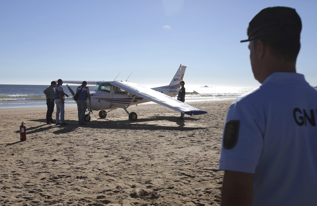 A policemen looks at coastguard officers check a small plane after an emergency landing on Sao Joao beach in Costa da Caparica, outside Lisbon, Wednes...