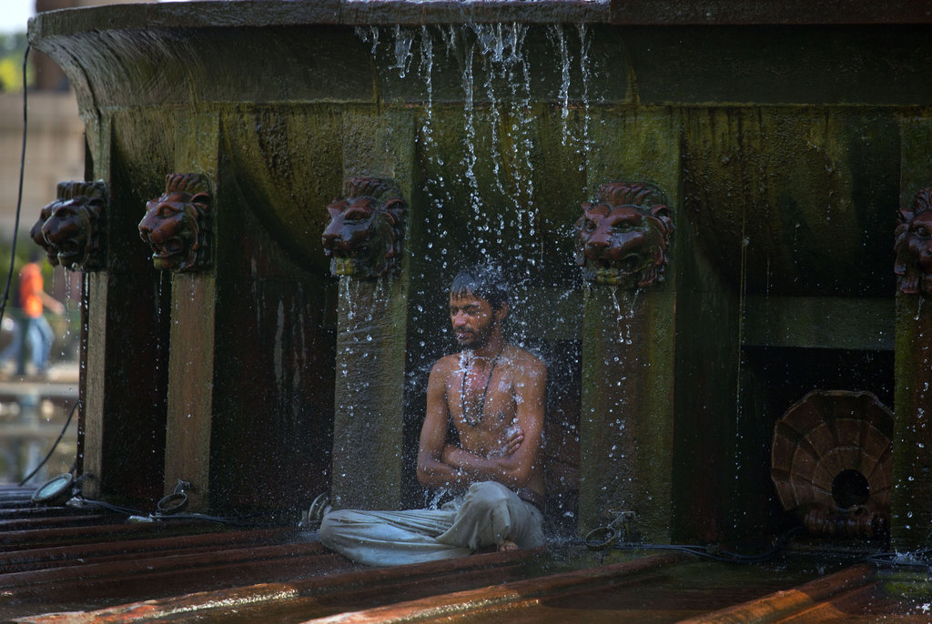 FILE- In this May 2, 2016 file photo, an indian man cools himself under a public fountain on a hot afternoon in New Delhi, India. A new study suggests...
