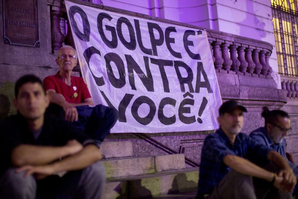 """Demonstrators sit next to a banner that reads in Portuguese """"The Coup is against you"""" in Rio de Janeiro, Brazil, Wednesday, Aug. 2, 2017. Demonstratio..."""