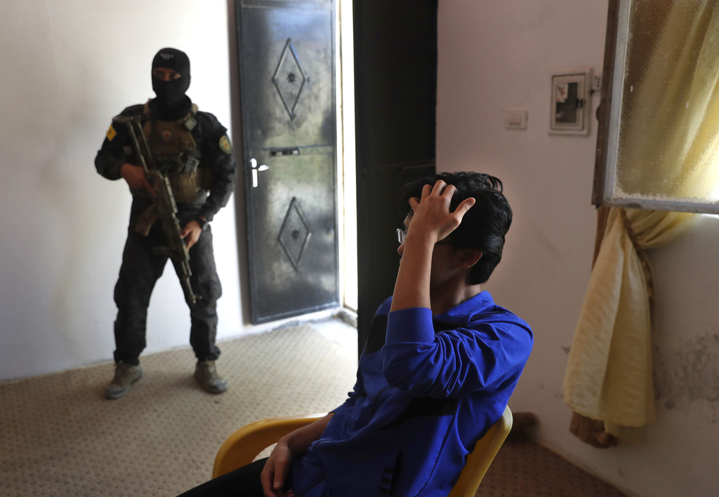 In this picture taken on Friday, July 21, 2017, a Kurdish soldier stands guard next to an Indonesian man suspected of Islamic State membership in Koba...