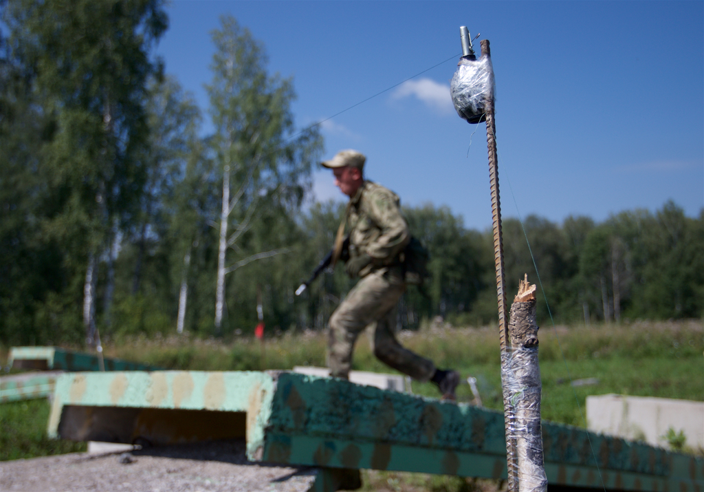 A Russian soldier runs looking for a booby trap during a team's run at the Army Scout Masters competition, part of Army Games, outside Novosibirsk, 29...