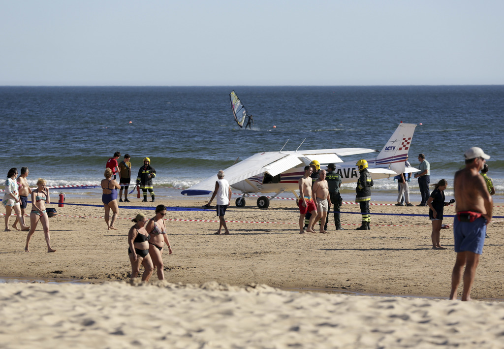 People walk past a small plane resting by the sea after an emergency landing at Sao Joao beach in Costa da Caparica, outside Lisbon, Wednesday, Aug. 2...