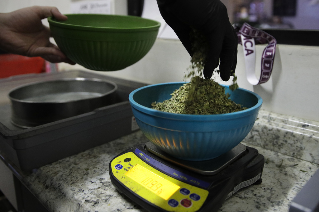 In this June 27, 2017, photo, an employee weighs sifted pot leaves to make joints at the Higher Path medical marijuana dispensary owned by Jerred Kilo...