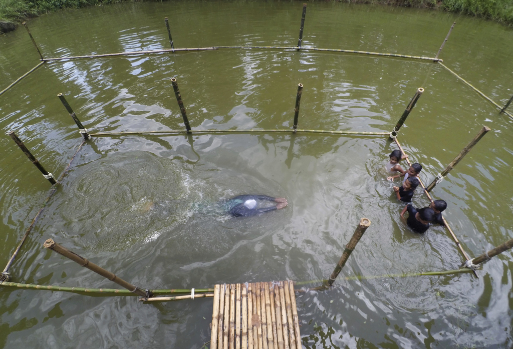 In this July 14, 2017 photo, a Bangladeshi trainer shows a swimming technique, as children watch during a swimming training session at a pond in the S...