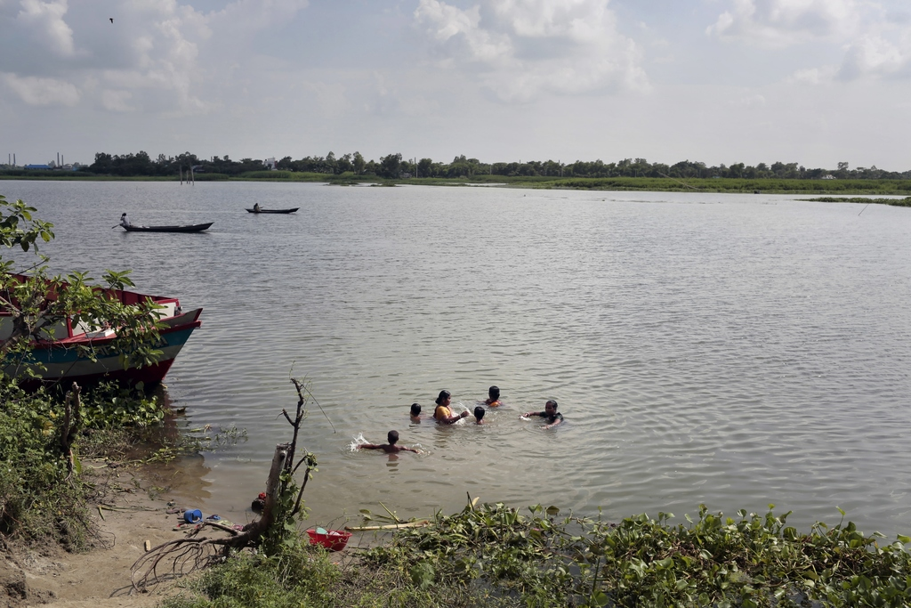 In this July 28, 2017 photo, Bangladeshi women and children take a bath in the river Burignaga in Noyadda village, Keraniganj, near Dhaka, Bangladesh....