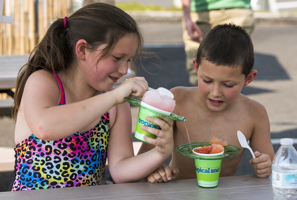Skyler Jennings shares a taste of her shaved ice with her brother, Preston, at Tropical Sno, a seasonal spot in Vancouver, Wash., Wednesday, Aug. 2, 2...