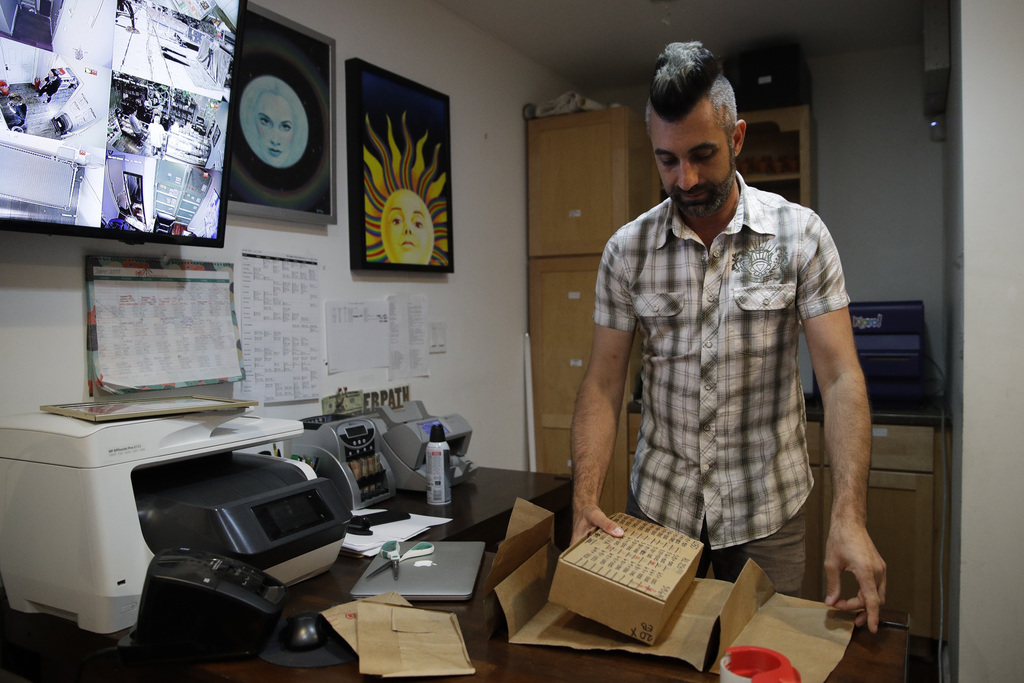 In this June 27, 2017, photo, Jerred Kiloh, owner of the Higher Path medical marijuana dispensary, wraps a package containing more than $40,000 in cas...