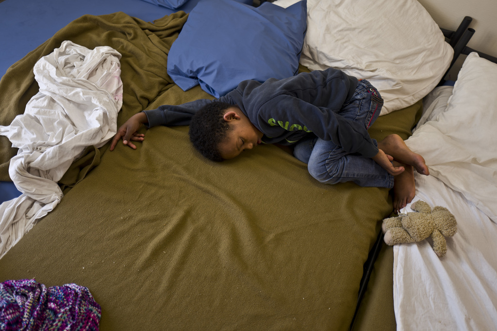 In this Friday, July 7, 2017 photo, Eritrean migrant Solomun Drat, 7, sleeps on a bed at his family's room in the former prison of Bijlmerbajes in Ams...