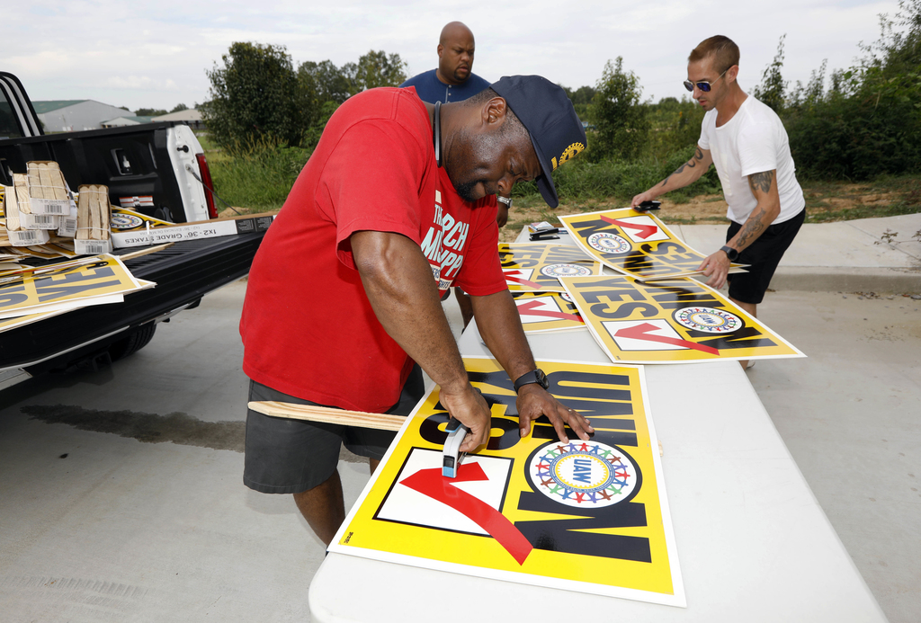 In this Tuesday, Aug. 1, 2017, photo, UAW member Albert Byrd, of Detroit, staples a double-sided yard sign, while CWA members Tim Case, right and Jero...