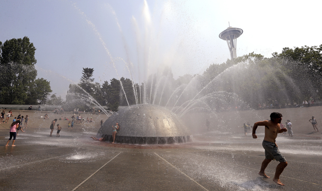 A man races away as a jet begins to spray toward him at the International Fountain at the Seattle Center during a heat wave Wednesday, Aug. 2, 2017, i...