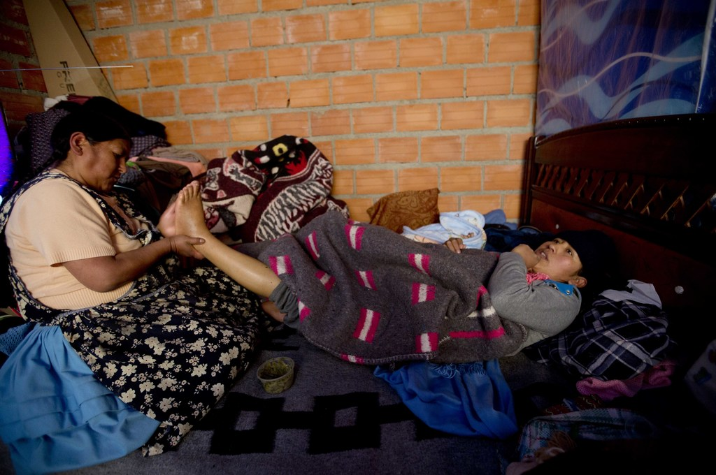 In this June 20, 2017 photo, midwife Ana Choque massages the feet of Mariana Limachi two weeks after delivering Limachi's first child at her home in E...