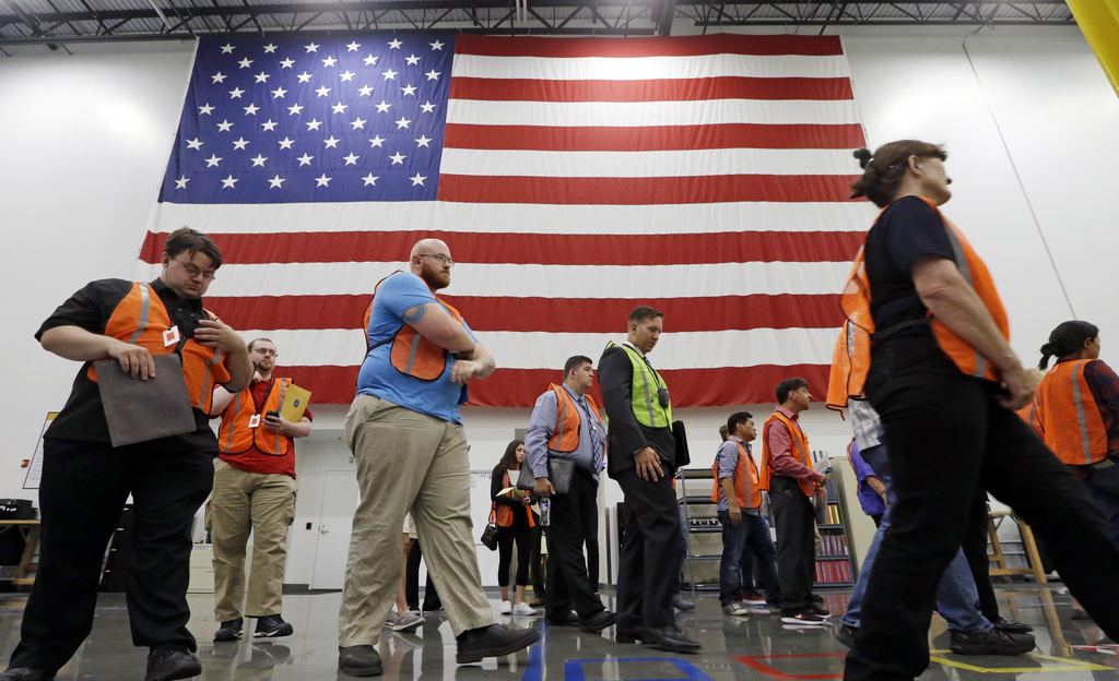 The first group of applicants walks past a giant American flag as they begin a site tour during a job fair, Wednesday, Aug. 2, 2017, at an Amazon fulf...