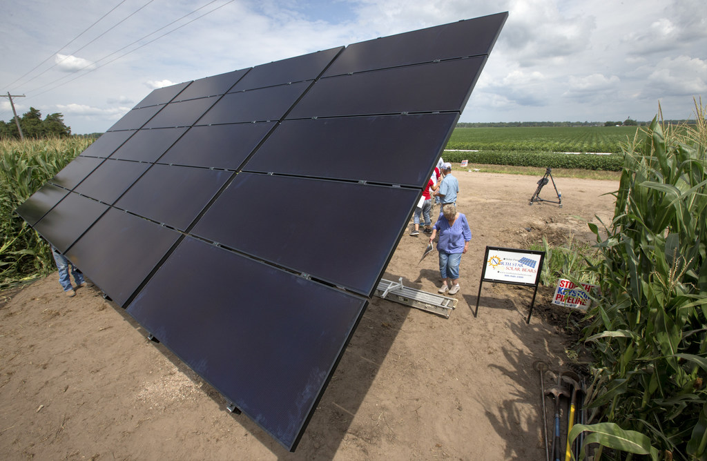 In this July 29, 2017 photo, an array of solar panels is seen on the land of corn farmer Jim Carlson of Silver Creek, Ne., in the proposed path of the...