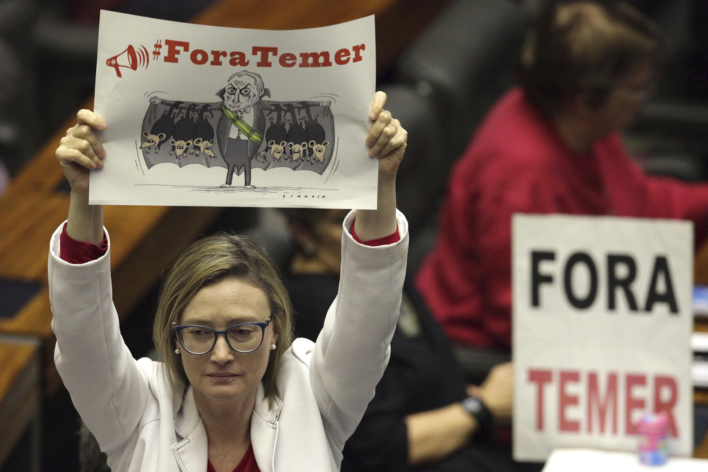 """Representative Maria do Rosario holds up a poster depicting Brazil's President Michel Temer, with a message that reads in Portuguese: """"Temer Out"""" duri..."""