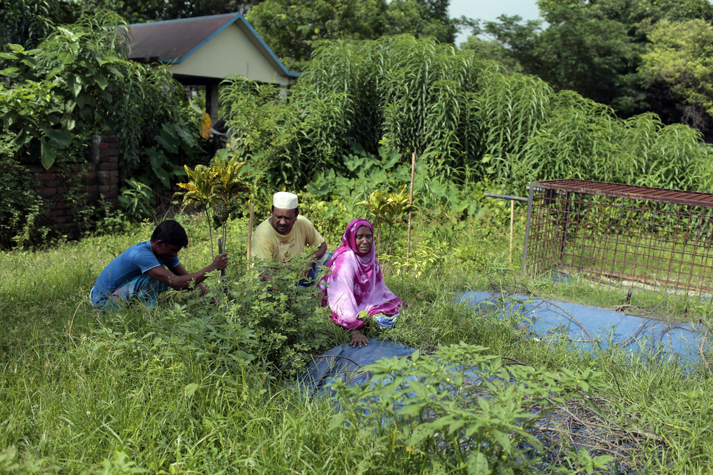 In this July 28, 2017 photo, Bangladeshi woman Samela Begum, right, cries near the graves of her two sons who drowned in a swamp in May, as her husban...