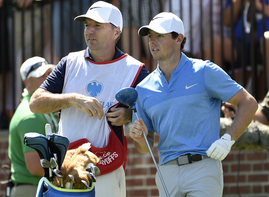 FILE - In this Aug. 28, 2016 photo, Rory McIlroy of Northern Ireland, right, and his caddy, J. P. Fitzgerald, look down the fairway before McIlroy tee...