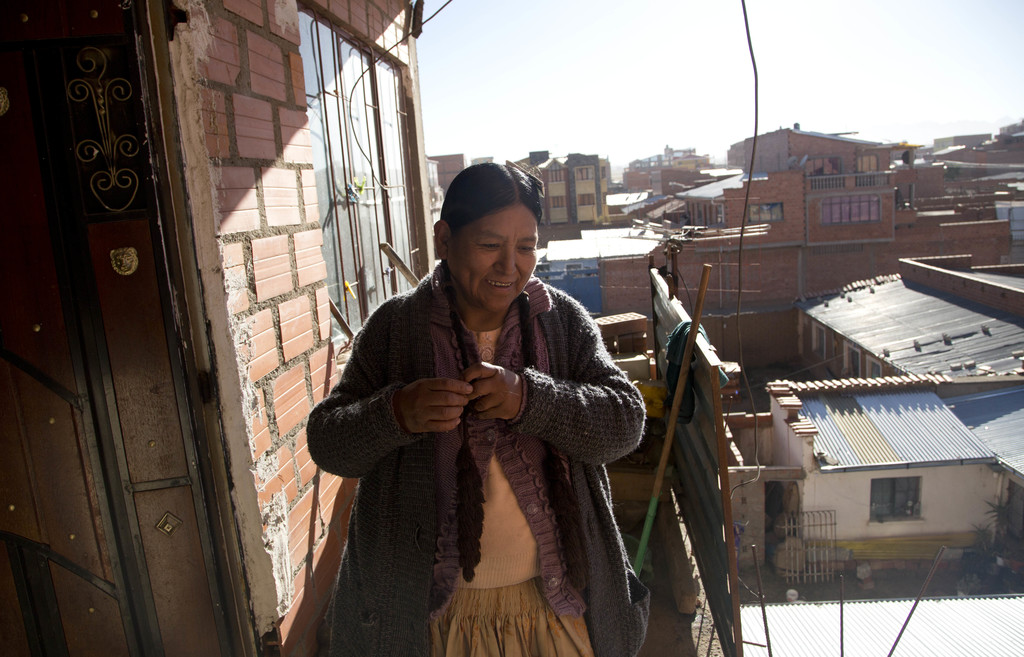In this July 20, 2017 photo, midwife Ana Choque braids her hair after getting home from a prenatal care visit at a patient's home in El Alto, Bolivia....