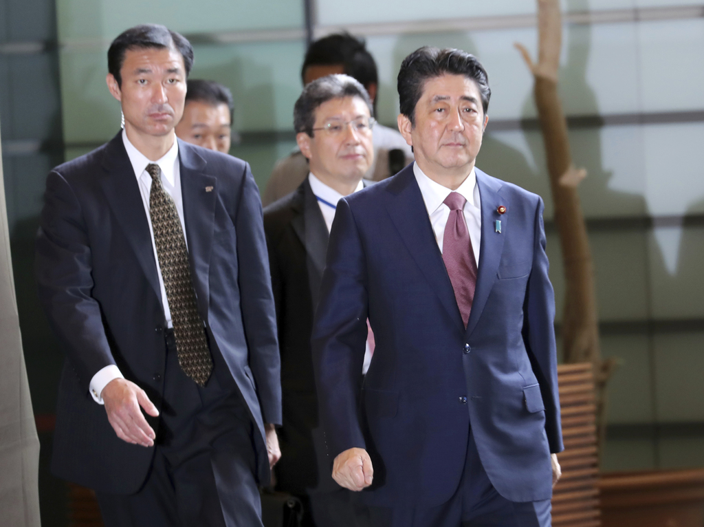 Japan's Prime Minister Shinzo Abe, right, enters his official residence in Tokyo Thursday, Aug. 3, 2017. Abe will reshuffle his Cabinet to replace som...