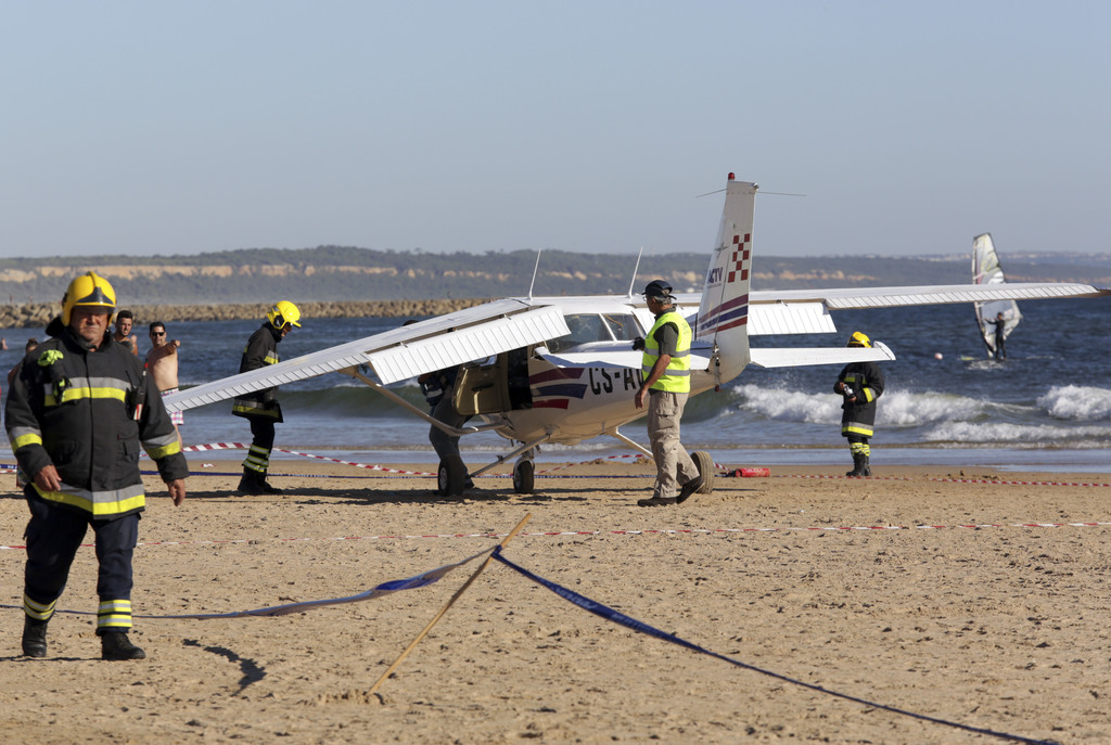 Firefighters stand next to a small plane after an emergency landing on Sao Joao beach in Costa da Caparica, outside Lisbon, Wednesday, Aug. 2, 2017. T...