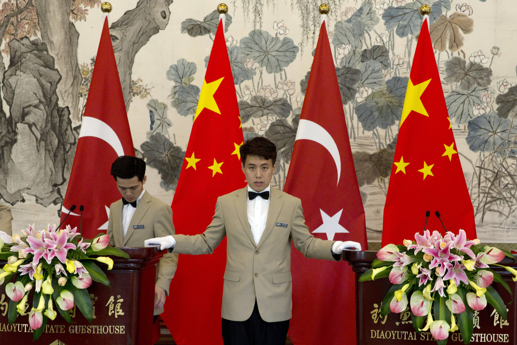 An attendant prepares the podiums for a joint press conference between Chinese Foreign Minister Wang Yi and Turkey Foreign Minister Mevlut Cavusoglu, ...