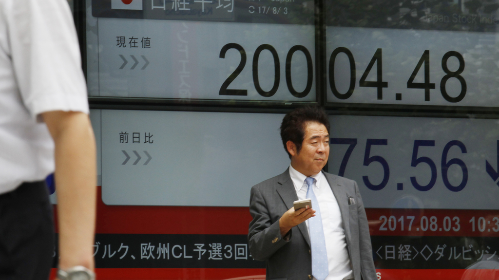 A man stands in front of an electronic stock board of a securities firm in Tokyo, on Thursday, Aug. 3, 2017. Asian markets mostly fell Thursday as the...