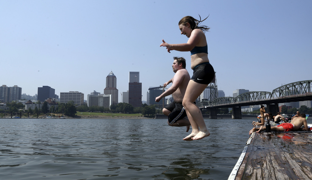 Jamie Downey, right, and Joe Feuerborn leap into the Willamette River with the downtown skyline visible across the river in Portland, Ore., Wednesday,...