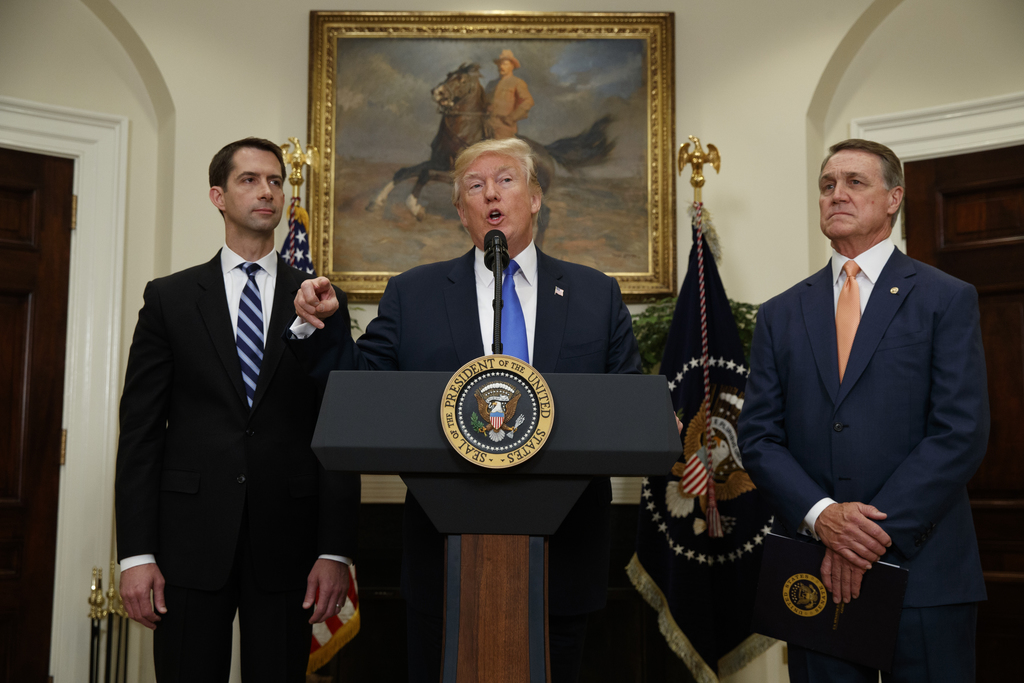 President Donald Trump, flanked by Sen. Tom Cotton, R- Ark., left, and Sen. David Perdue, R-Ga., speaks in the Roosevelt Room of the White House in Wa...