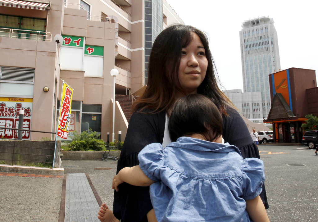 In this Tuesday, Aug. 1, 2017, photo, Misaki Honna, carrying her 10-month-old daughter, speaks to The Associated Press near Yokosuka-chuo Station in Y...