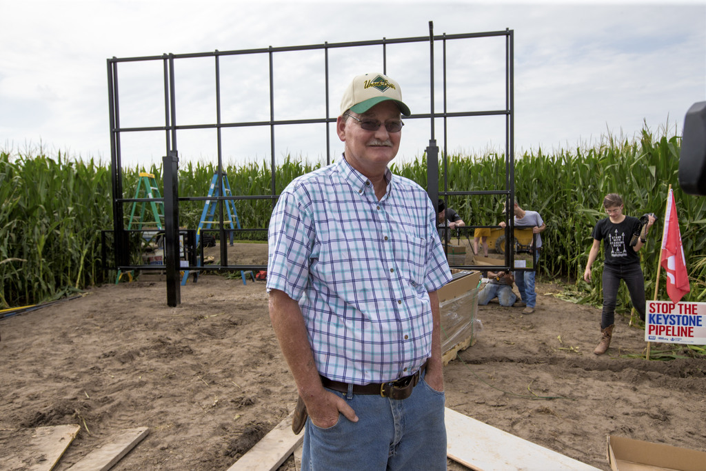 In this July 29, 2017 photo, corn farmer Jim Carlson of Silver Creek, Ne., waits to be interviewed by a television reporter while standing in front of...