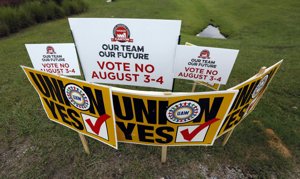In this Tuesday, Aug. 1, 2017, photo, UAW members use their signs to block Nissan company signs at one of the entrances to the vehicle assembly plant ...