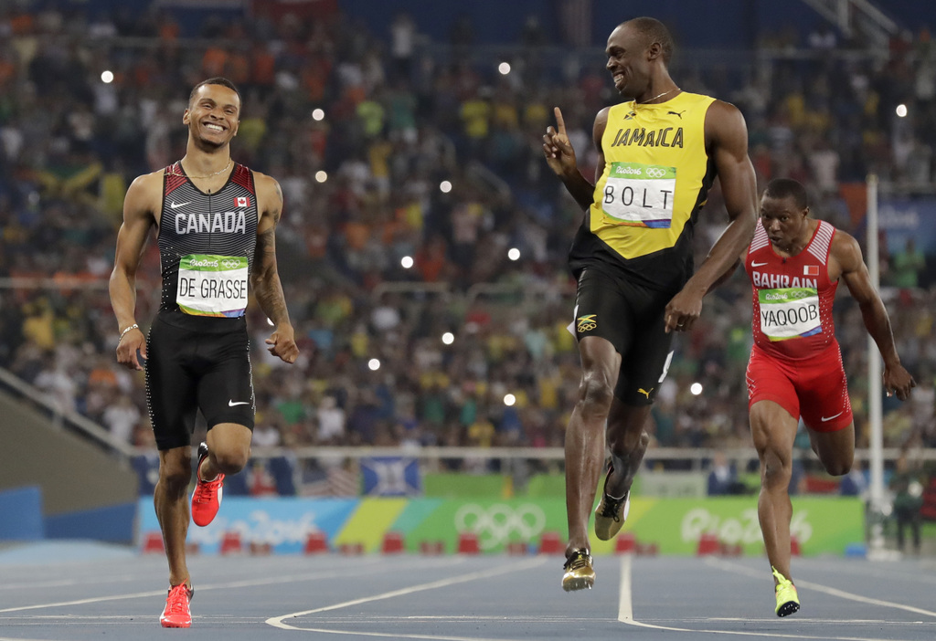 FILE - In this Aug. 17, 2016, file photo, Jamaica's Usain Bolt, right, gestures towards Canada's Andre De Grasse after the finish of the men's 200-met...