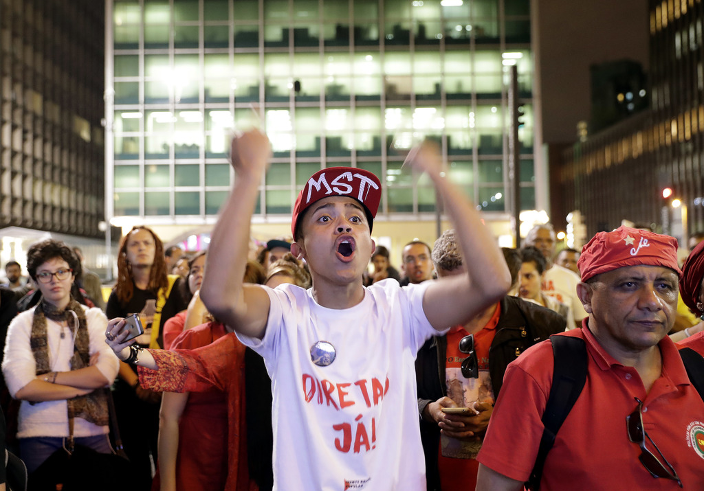 """A demonstrator wearing a shirt carrying the Portuguese message: """"Elections Now"""" protests as he watches live images of the lower chamber of Brazil's Co..."""