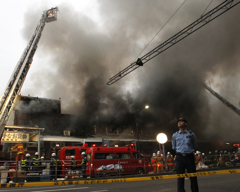 Firefighters attempt to extinguish a fire at Tsukiji Fish Market on Thursday, Aug. 3, 2017, in Tokyo. No injuries were reported. (AP Photo/Sherry Zhen...