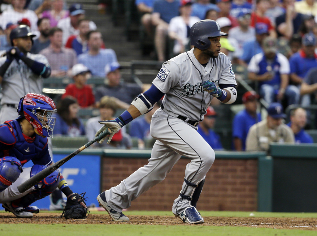 Seattle Mariners' Robinson Cano follows through on a single up the middle as Texas Rangers' Robinson Chirinos watches during the third inning of a bas...