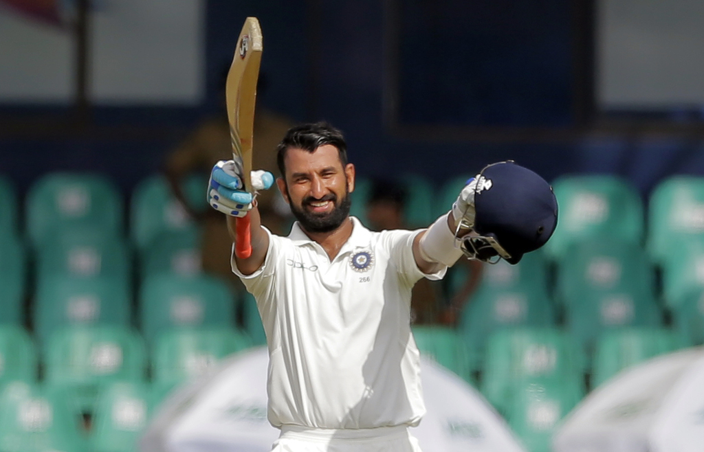 India's Cheteshwar Pujara raises his bat and helmet to celebrate scoring a century during their second cricket test match against Sri Lanka in Colombo...
