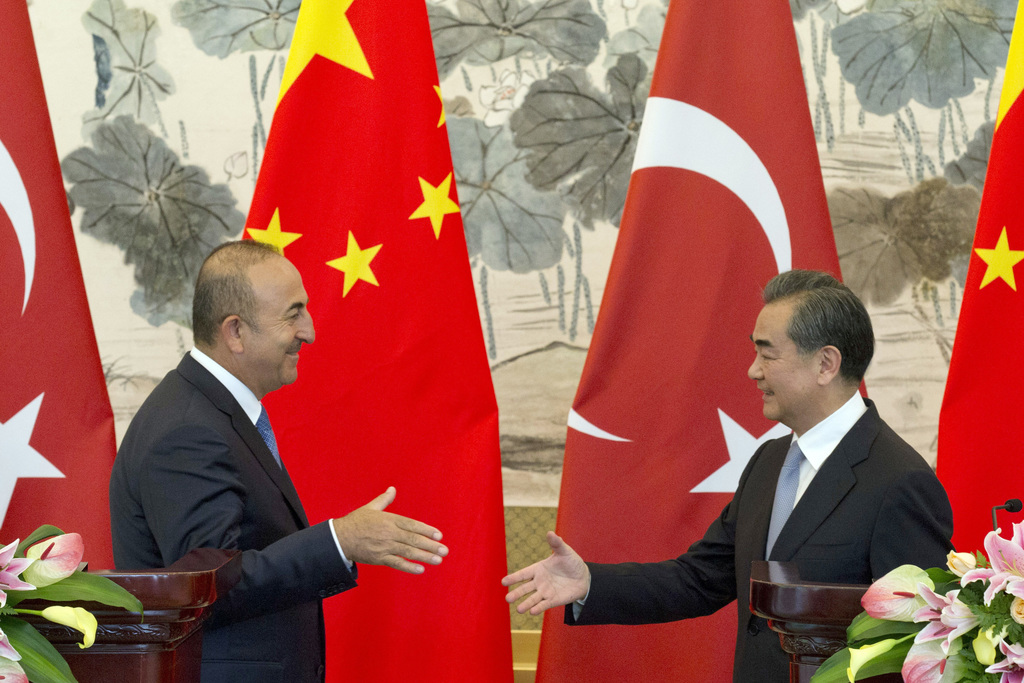 Chinese Foreign Minister Wang Yi at right shakes hands with Turkish Foreign Minister Mevlut Cavusoglu after a joint press conference held at the Diaoy...