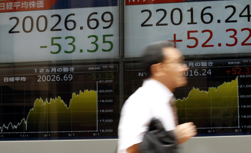 A man hurries past an electronic stock board of a securities firm in Tokyo, Thursday, Aug. 3, 2017. Asian markets mostly fell Thursday as the rally fr...