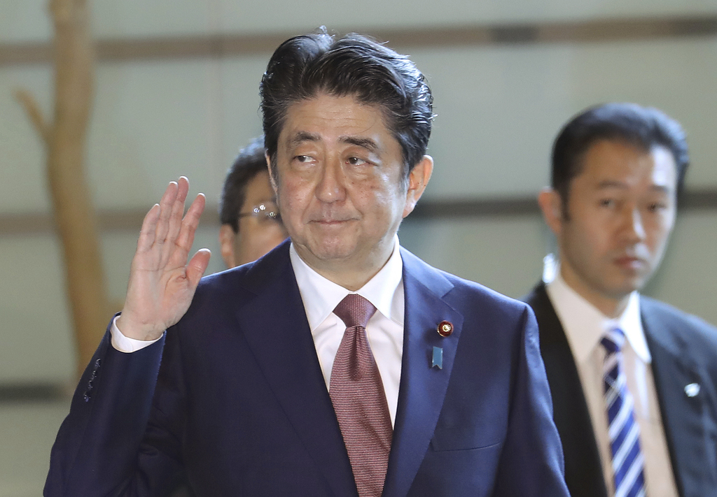 Japan's Prime Minister Shinzo Abe, left, enters his official residence in Tokyo Thursday, Aug. 3, 2017. Abe will reshuffle his Cabinet to replace some...