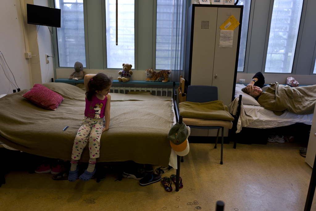 In this Friday, June 30, 2017 photo, refugee Nadia Gattas, 82, from Deir el-Zour, Syria, right, lies on a bed in her room in the former prison of Bijl...