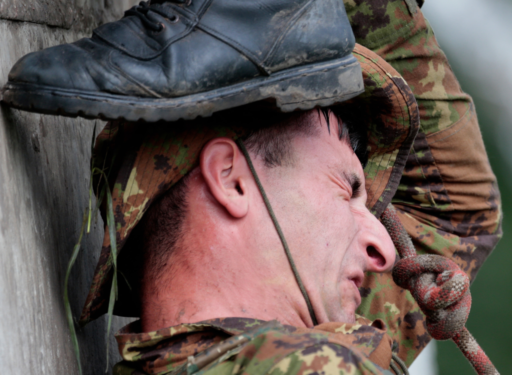 An Armenian soldier grimaces during his team's run during the Army Scout Masters competition, part of Army Games, outside Novosibirsk, 2900 km (some 1...