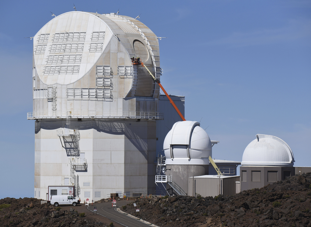 FILE - In this June 24, 2016, file photo, workers use a lift to scale the exterior the Daniel K. Inouye Solar Telescope at the summit of Haleakala. Fi...