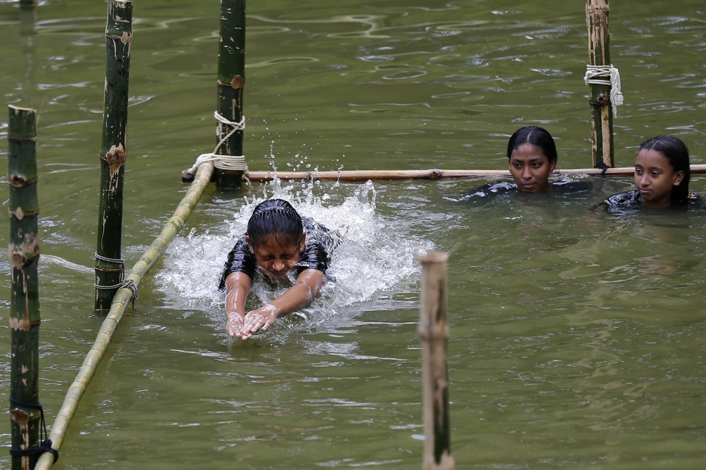 In this July 14, 2017 photo, a Bangladeshi girl jumps from the starting block as she attends a swimming training session at a pond in the Shishu Polli...