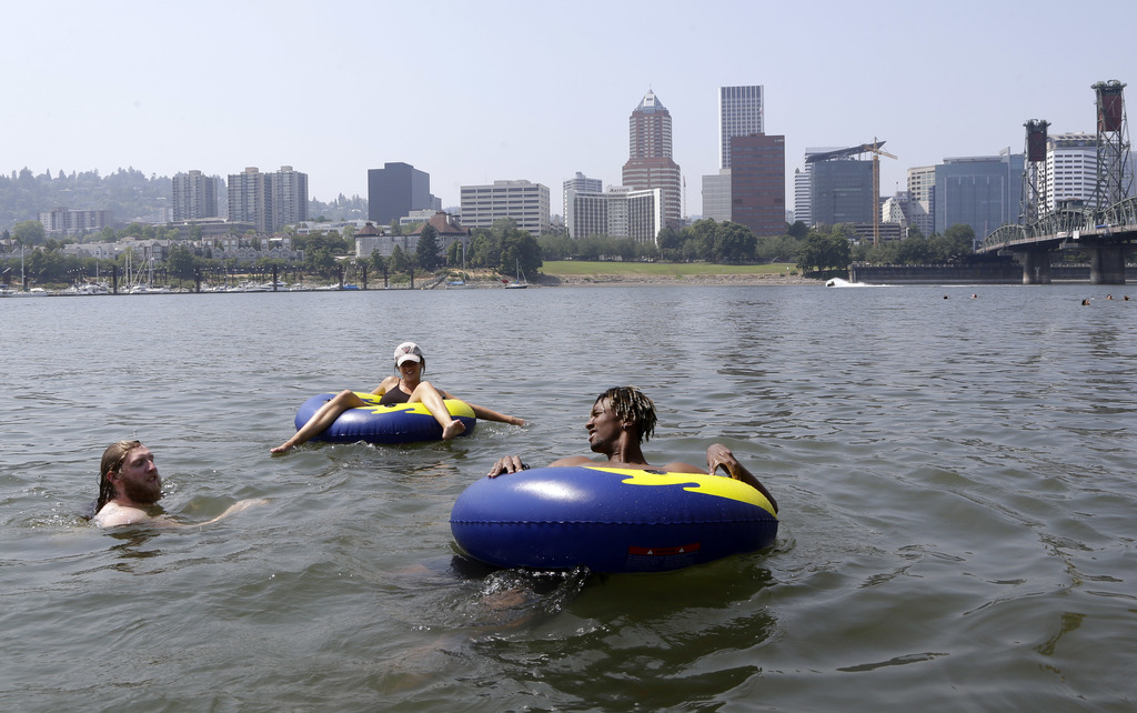 People cool off in the Willamette River with the downtown skyline visible in the background in Portland, Ore., Wednesday, Aug. 2, 2017. Scorching temp...