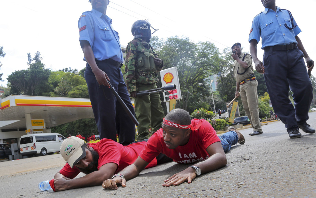FILE - In this Tuesday, Dec. 1, 2015 file photo, police and security forces arrest protest leader Boniface Mwangi, center, and another demonstrator du...