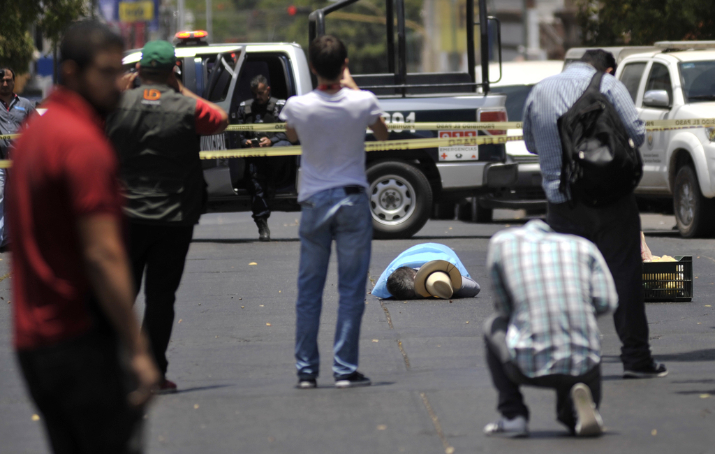 FILE - In this May 15, 2017 file photo, people take photos of the body of slain journalist Javier Valdez, in Culiacan, Mexico. Mexico is now the world...