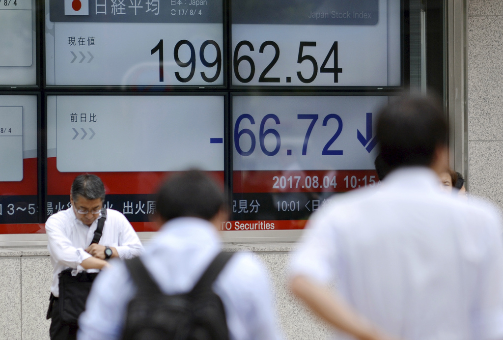Pedestrians wait in front of an electronic stock board showing Japan's Nikkei 225 index at a securities firm in Tokyo, Friday, Aug. 4, 2017. Most Asia...
