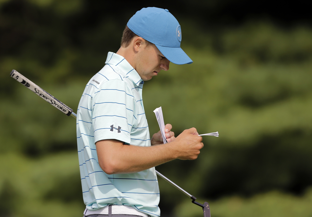 Jordan Spieth looks at his yardage book on the first hole during the second round of the Bridgestone Invitational golf tournament at Firestone Country...